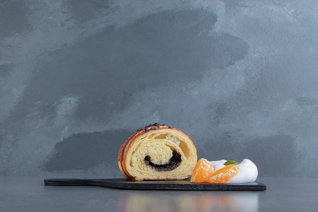 Half-cut croissant with tangerine slices on black cutting board.