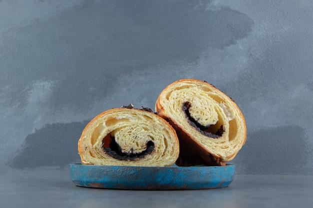 Croissant tagliati a metà con cioccolato su piatto blu.