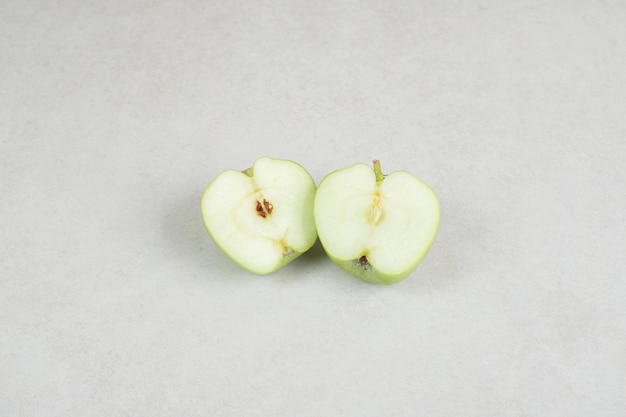 Half cut fresh apples on gray surface