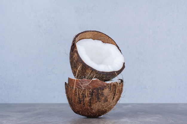Noci di cocco fresche tagliate a metà sul tavolo di pietra.