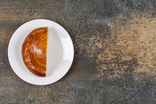 白い皿にハーフカットの焼きたてのペストリー。