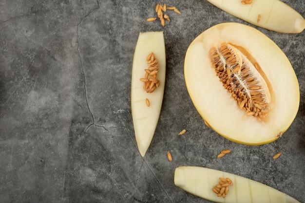 Melone dolce fresco tagliato a metà posto su una superficie di marmo.