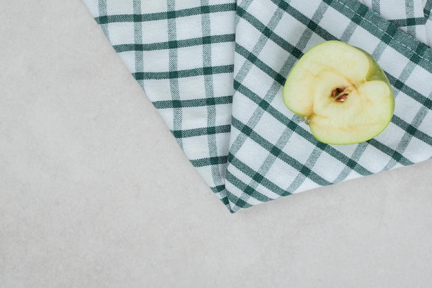 Half cut green apple on striped tablecloth