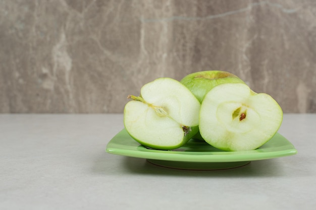 Half cut green apples on green plate.