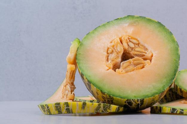 Melone verde tagliato a metà sul tavolo bianco.