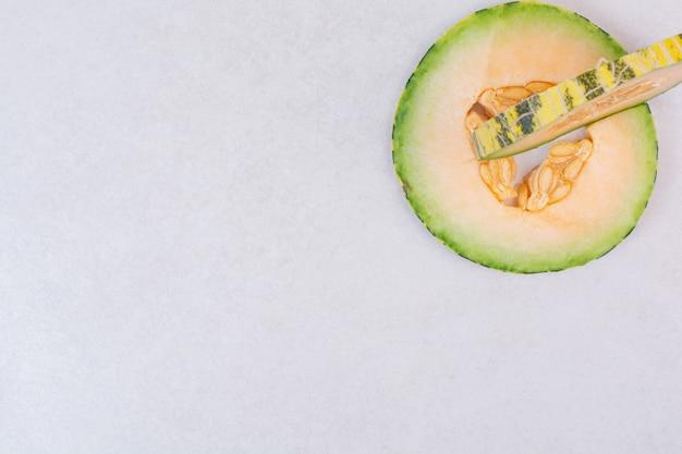 Melone verde tagliato a metà con semi sulla superficie bianca