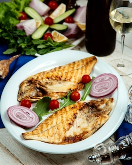 Half-cut grilled fish served with onion and cherry tomato