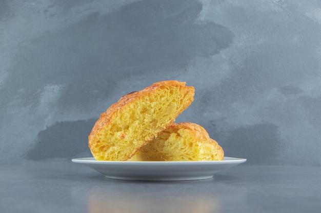 Pasta fatta in casa tagliata a metà su piatto bianco.
