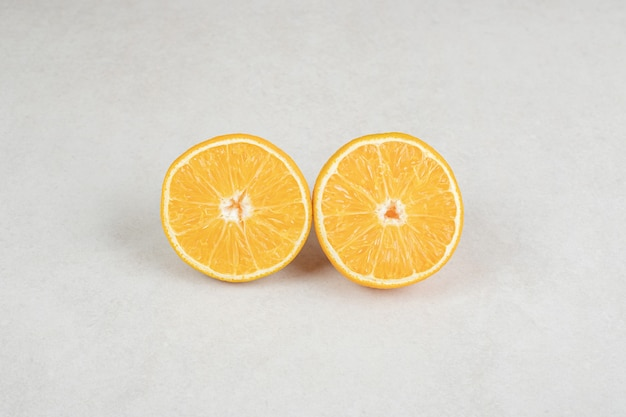 Half cut juicy orange on gray surface