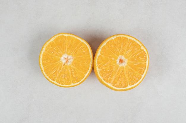 Половинки сочного апельсина на серой поверхности.