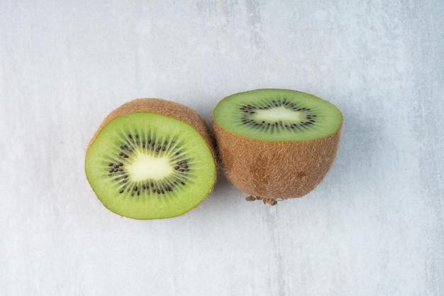 Half cut kiwi fruit on stone background. high quality photo