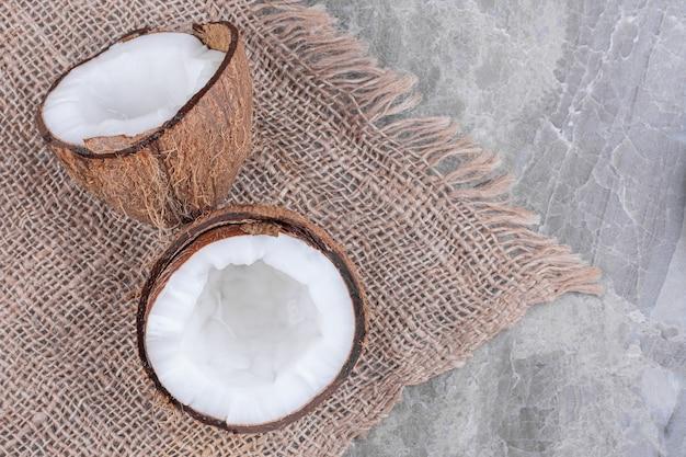 신선한 건강한 코코넛의 절반을 잘라 돌 표면에 놓습니다.