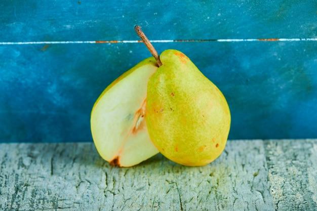 青の背景に熟した梨のハーフカット。