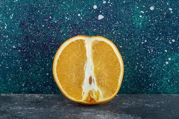 Разрезанный наполовину апельсин на синем столе.