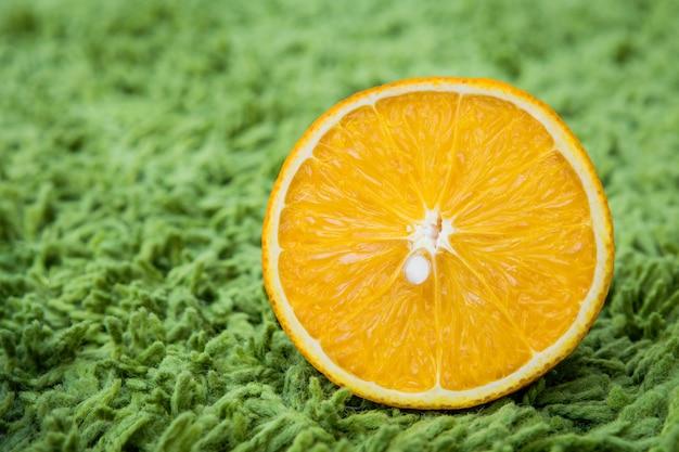 Half cut orange texture on green floor.