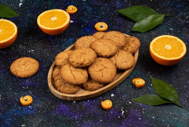 Half cut oranges and half cut homemade cookies on wooden board over space surface.