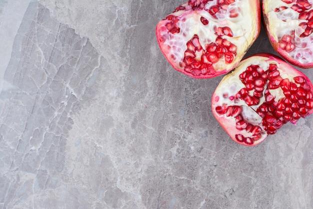 Наполовину отрезанные красные гранаты на каменном фоне. Бесплатные Фотографии