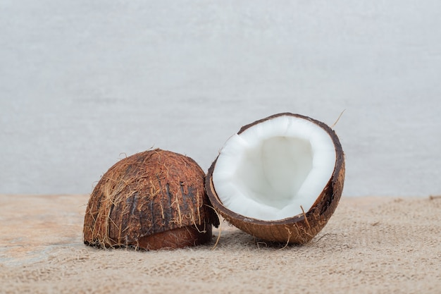 Половина спелых кокосов на мраморном столе с мешковиной.