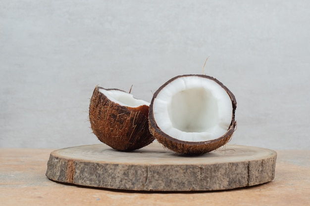 Noci di cocco mature tagliate a metà sul pezzo di legno.