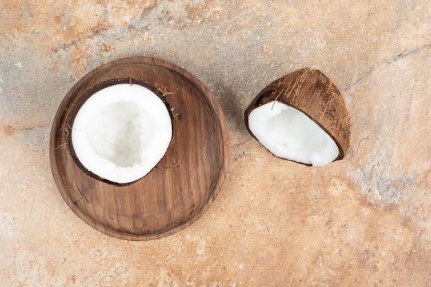 Noci di cocco mature tagliate a metà sul piatto di legno.