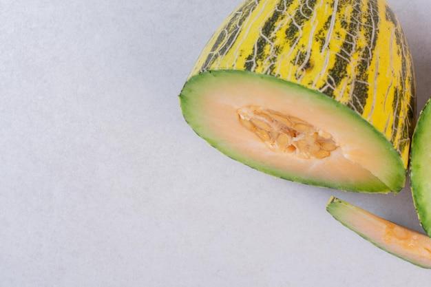 Melone maturo tagliato a metà sul tavolo bianco.