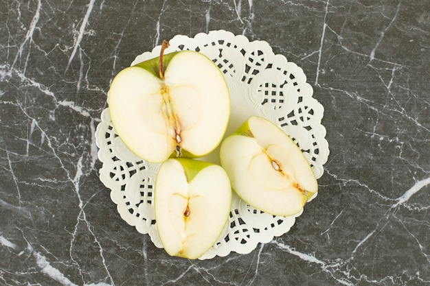 Mela verde tagliata a metà e affettata. mela verde biologica su grigio.