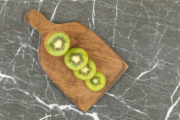 Half cut and sliced kiwi on wooden cutting board.