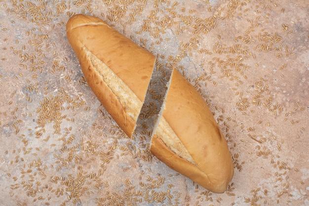 Pane di grano tagliato a metà con orzo su superficie di marmo