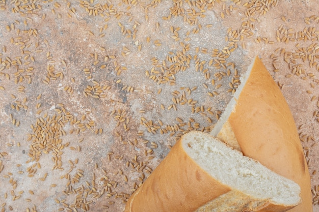 Half cut wheat bread with barley on marble surface