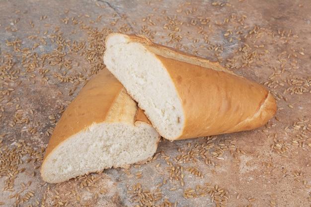 Половина нарезанный пшеничный хлеб с ячменем на мраморной поверхности