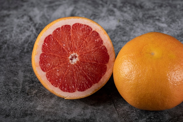 Half cut and whole grapefruit on a black backdrop
