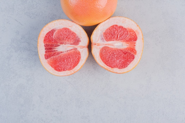 Half cut and whole grapefruit on grey background.