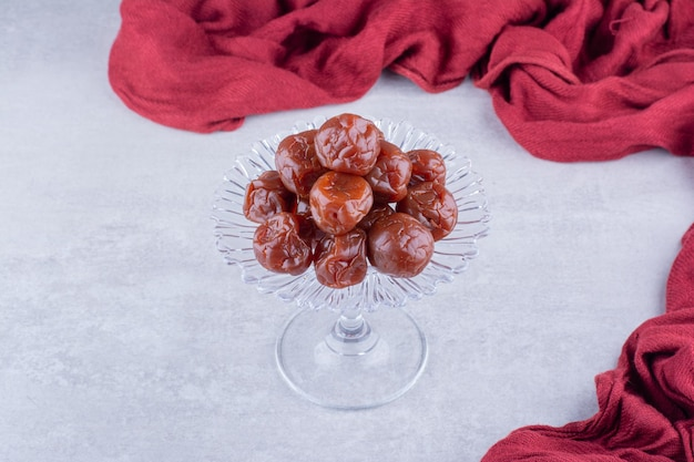 Half dried brown sour cherries in a cup on concrete background. high quality photo