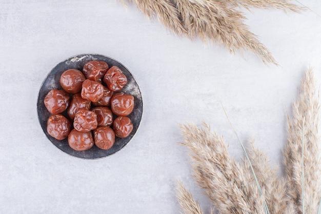 Полусушеные коричневые вишни в чашке на бетонной поверхности