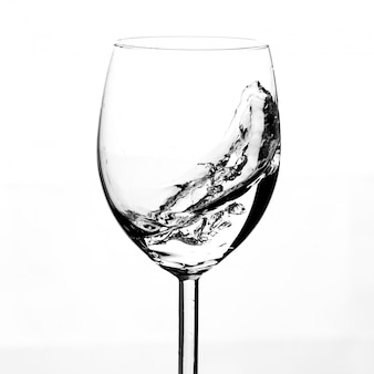 Half empty glass with water in motion