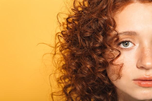 穏やかな巻き毛の赤毛の女性の半分の顔をクローズアップ