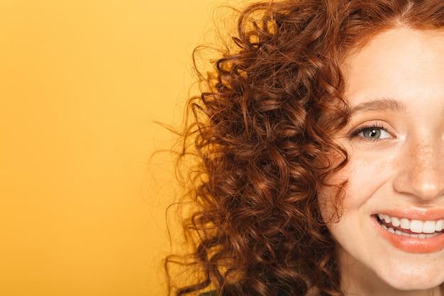 半分の顔は笑顔の巻き毛の赤毛の女性のクローズアップ