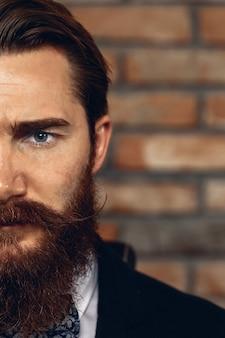 口ひげとあごひげを身に着けているスーツを着た真面目な男性の半分の顔のクローズアップの肖像画。レンガの壁を背景に。