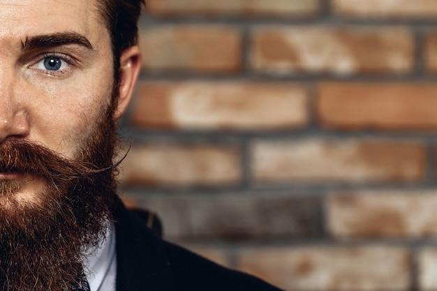 口ひげとひげを身に着けているスーツを着たハンサムな男の半分の顔のクローズアップの肖像画。レンガの壁を背景に。