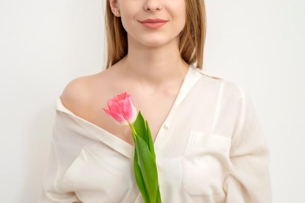 흰색 배경에 대해 하나의 튤립과 아름다운 백인 젊은 여자의 절반 얼굴