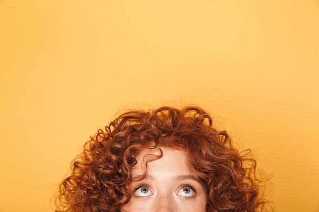 コピースペースを見上げる若い女性の半分の顔