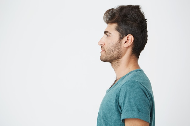 Half-face  portrait of beautiful spanish man, in casual blue t-shirt, with trendy hair and beard, showing his profile and looking to the left. copy space.