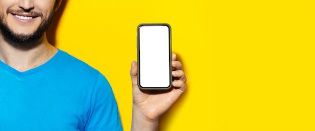 노란색 벽에 빈 화면으로 스마트 폰 들고 남자의 절반 얼굴 초상화