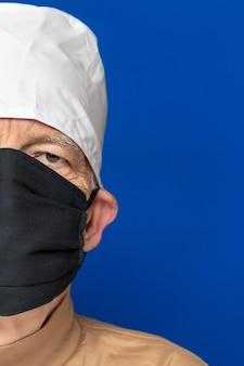 얼굴이 반쪽인 노인 의사는 검은색 수술용 얼굴 마스크, 흰색 의료 모자를 쓰고 파란색 배경에 서서 카메라를 꿰뚫어보고 있습니다. 클로즈업 헤드 샷입니다. 개념 예방 보호입니다.