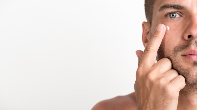 Half face of shirtless young man applying cream on his face against white background