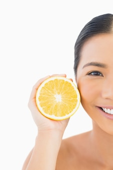 Half face of smiling pretty woman with orange