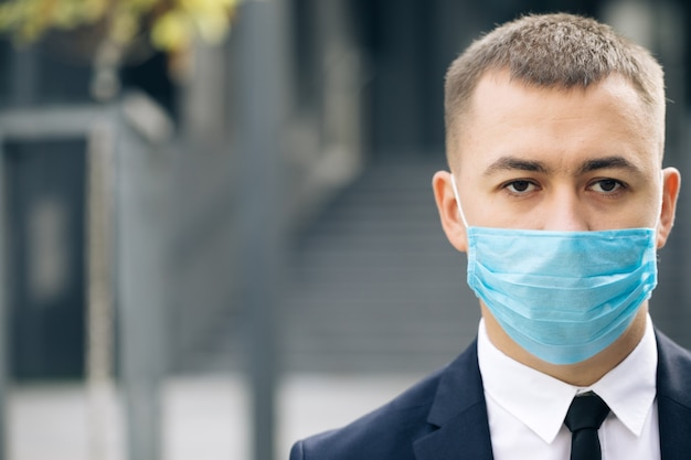 Half face of upset caucasian young handsome man in medical mask