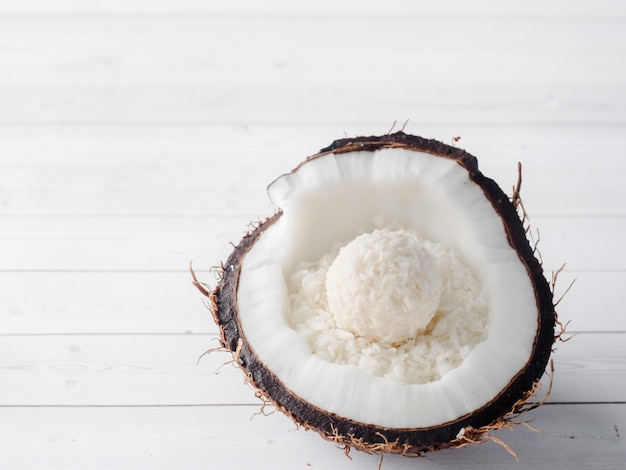 Half of the fresh organic coconut with coconut and chocolate candy inside on wooden background.