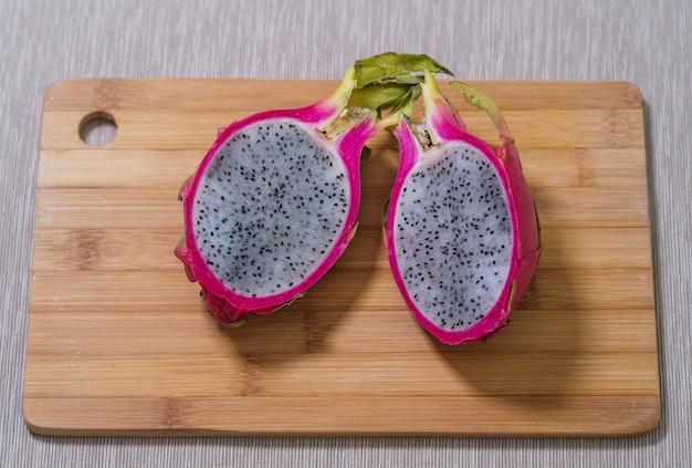 Half of fresh pitaya or dragon fruit lie on the table