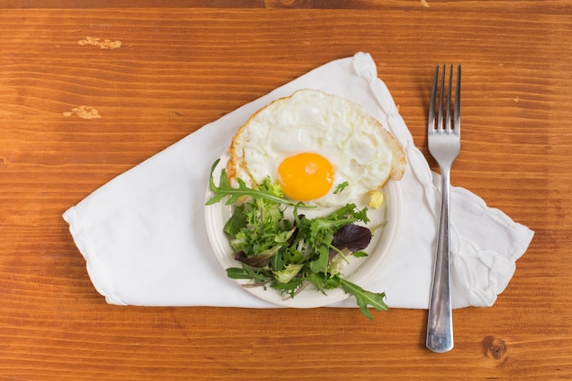 Half fried egg with salad on plate and fork over the white napkin against wooden textured backdrop